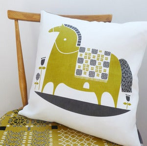 Image of rocking horse cushion in olive on white linen