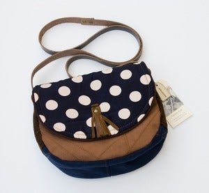 Image of - S O L D - a small cross body bag with a deep navy +baby pink polka dot flap
