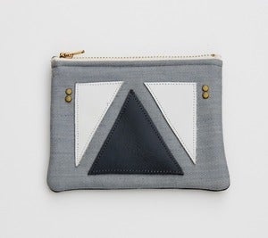 Image of small zipper pouch with geometric leather appliques and a metal zipper