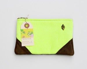 Image of small neon yellow zipper pouch with leather corners and a METAL zipper