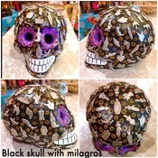 Image of Clay skulls with milagros